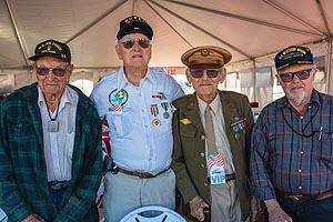 three elderly World War II Veterans standing for a portrait