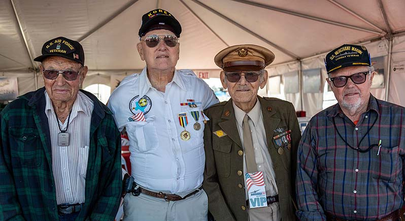 photo of four elderly veterans standing side by side wearing military caps and their wartime decorations