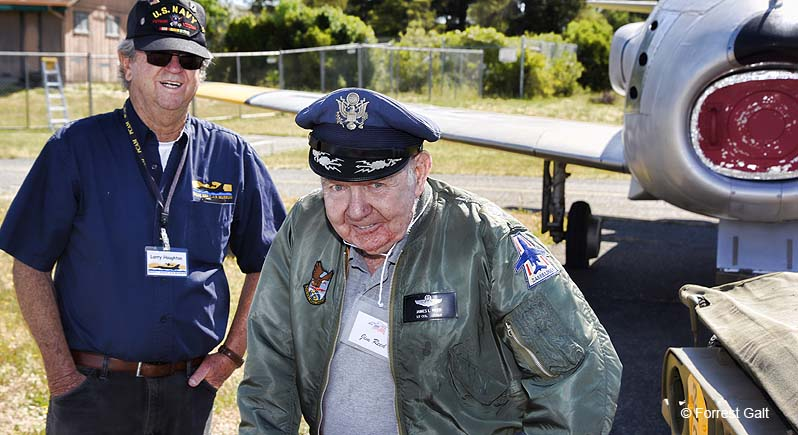 Photo of an elderly Veteran in his Air Force service cap and jacket, standing in front of an F-86 fighter plane