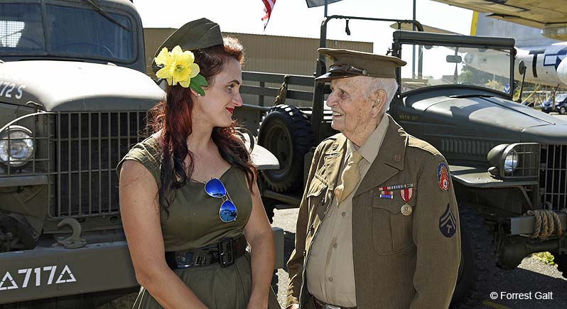 photo of elderly veteran in World War II era uniform with young woman dressed in military inspired clothing, standing in front of WWII vintage venicles