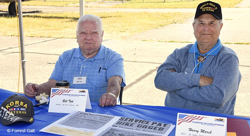 two elderly veterans sitting at a table with wartime memorabilia