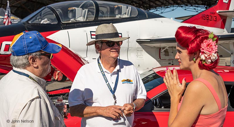 Two men and a woman talk together at the Wheels & Wings Car Show at the Pacific Coast Air Museum, with a jet trainer and Ford Mustang behind them.