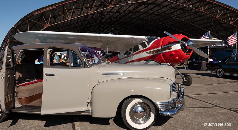 A classic sedan and Cessna 195 airplane at the Wheels & Wings Car Show at the Pacific Coast Air Museum