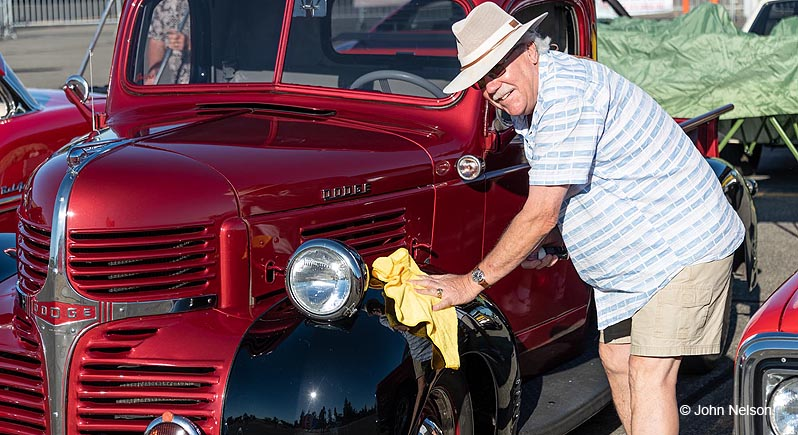 The proud owner of a red 1930s dodge pickup truck polishes the fenders at the Wheels & Wings Car Show at the Pacific Coast Air Museum