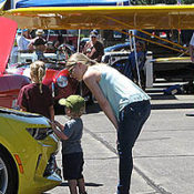 woman and toddler examining the engine of a yellow muscle car at a car show