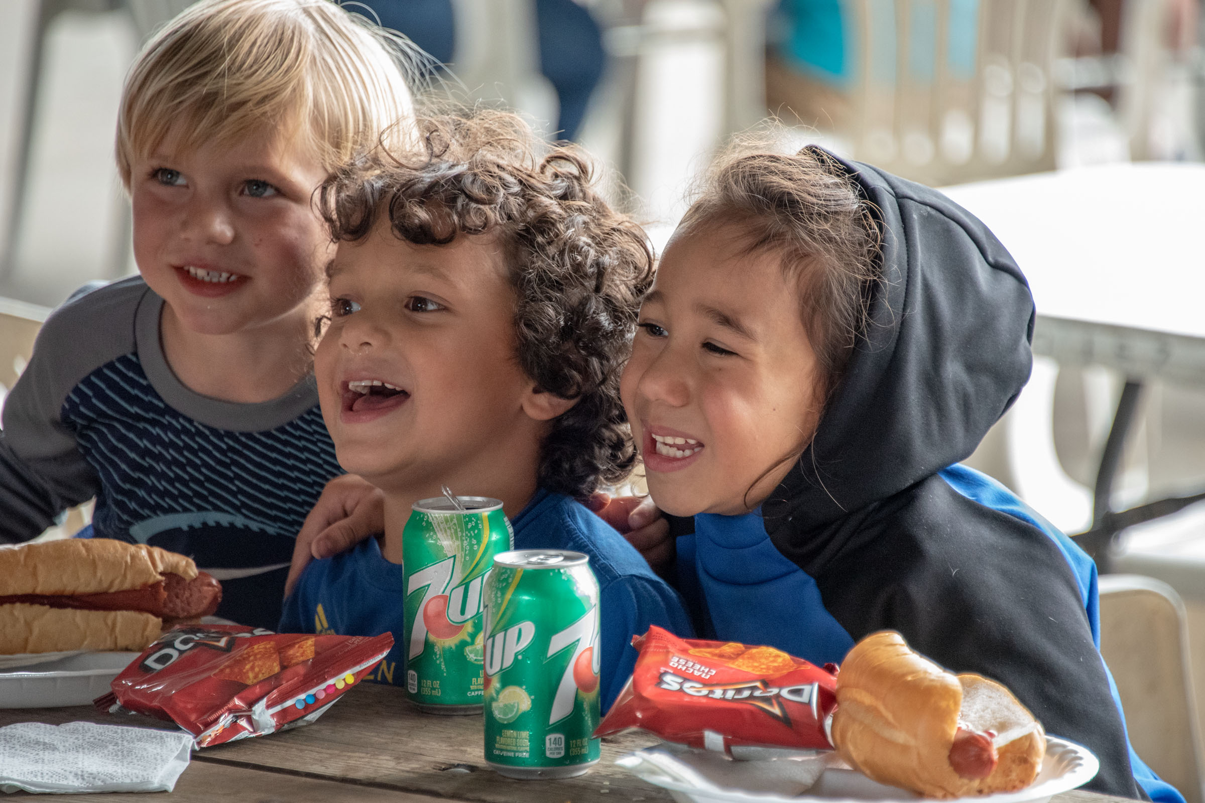 Kids smiling and eating hot dogs