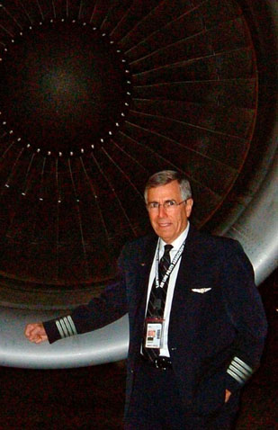 Retired US Navy Aviator Bob Bostick in airline captain's uniform standing in front of a jet engine